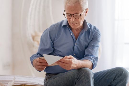 Moody cheerless man reading an old letter