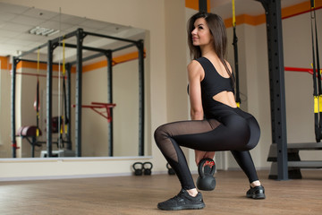 Beautiful woman squats with kettlebell at the gym