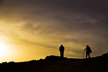 silhouettes on top of mountain in sunset