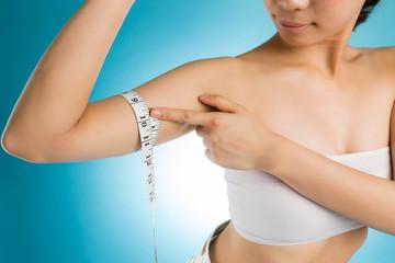 メジャーで二の腕を測る女性