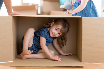 little girl inside box in new flat after moving