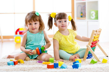 Children playing together. Toddler kid and baby play with blocks. Educational toys for preschool and kindergarten child. Little girls build toys at home or daycare.