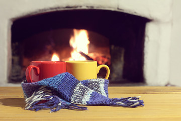 warming cozy pastime/ Red and yellow mugs in blue scarf on the background of warmed-up fireplace