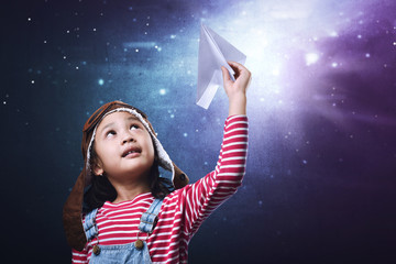 Beautiful asian little girl having fun with paper airplane toy