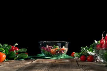 Bowl of salad on wooden board on dark background