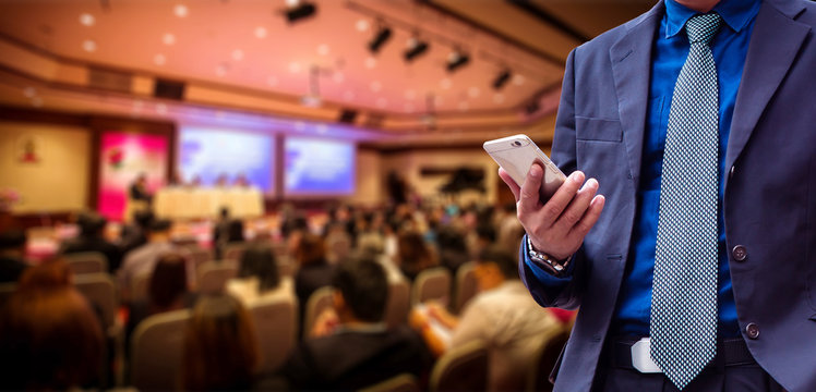 businessman using the mobile phone, blurred of conference hall or seminar room with attendee background.