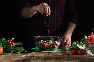 Man sprinkles salt salad of fresh vegetables on wooden table Wall mural