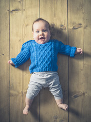 Happy surprised baby on wooden floor