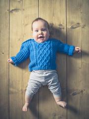 Happy surprised baby on wooden floor
