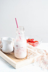 Healthy strawberry milkshake in glass bottle with ingredients on white table