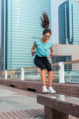 Young fit active woman bench jump squat jumping on city street. Fitness girl doing exercises outdoors.