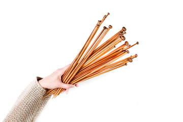 Bunch of brown bamboo wooden knitting needles in woman hand on white background. Top view