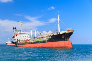 Oil tanker ship at sea on blue sky background