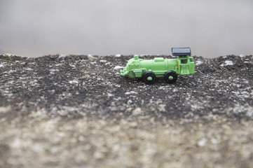 Green steel toy train in an asphalt background, conceptual photo