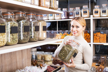 Woman selecting dried herbs
