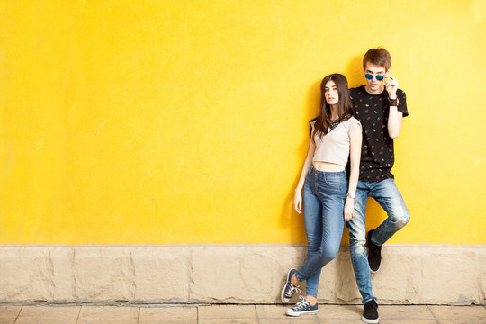 Young couple posing in fashion style on yellow wall. Lifestyle and relationship