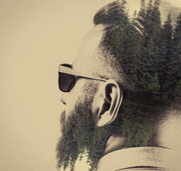Portrait of a bearded man in sunglasses, with a stylish haircut. Black and white. Image created using multiple exposures. Forest landscape is depicted on dark parts of image.
