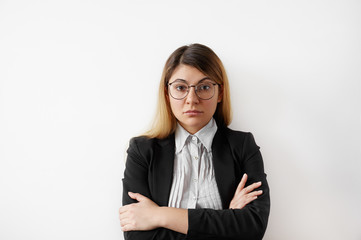 Portrait of successful young entrepreneur female in black suit and shirt wearing glasses looking confident and serious. Thoughtful young businesswoman standing staring at camera with folded arms