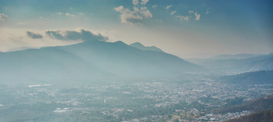 Foggy volcanic land of Guatemala / Antigua City from above