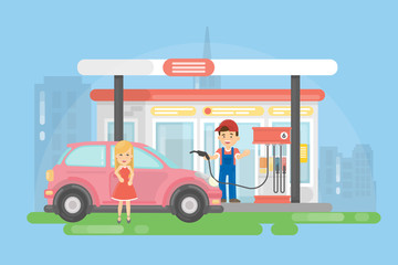 Urban gas station. Man in uniform helps young woman in red dress.