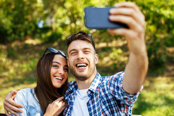 Young couple doing selfie on bench in the park