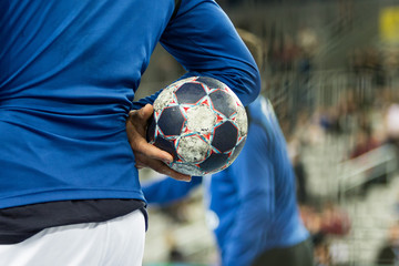 Player holding the ball, close up.
