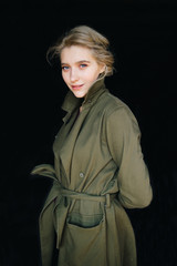 Portrait of lonely beautiful, cute, attractive, young, model blonde fashion student girl in green coat and curly hair posing at camera. Isolated on black. Tenderness and femininity. Pure beuaty. Angel