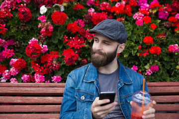 Bearded man with phone and smoothie