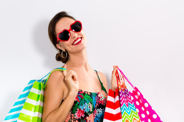 Happy young woman holding many shopping bags