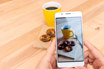 Using a mobile phone to photograph hot coffee and doughnuts in chocolate on a wooden background with copy space. Photos of drinks and food for advertising or social media. Template.