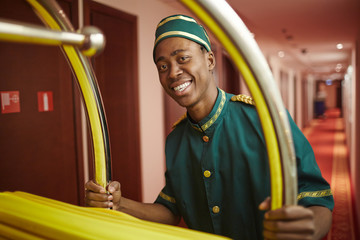Happy porter doing his work in hotel