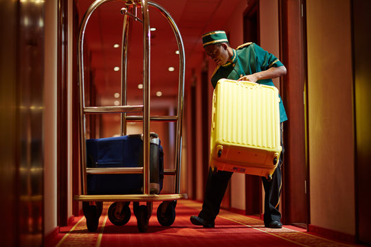 Hotel servant taking out suitcase with baggage from hotel room