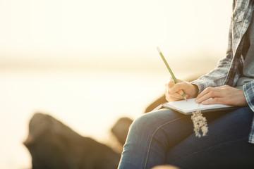 Obraz  woman writing on a journal about her hiking trip,flare light - fototapety do salonu