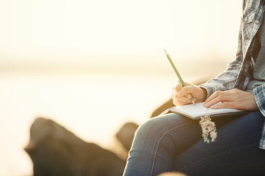 woman writing on a journal about her hiking trip,flare light
