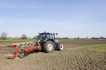 farmer ploughs filed with plough behind tractor near renswoude in the netherlands