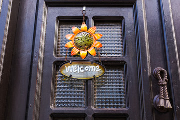 Welcome sign with flower on the door