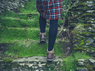 Woman in skirt walking up steps in nature