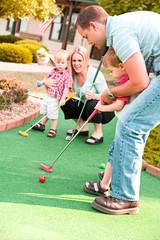 Golf: Dad Helps Little Boy Learn To Mini-Golf
