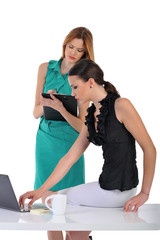 two young woman working together on laptop computer