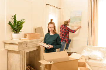 serious woman unpacking box and man hanging picture at new home
