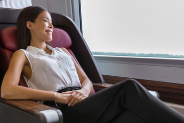 Happy commuter enjoying train travel to go to work in the morning. Asian woman enjoying view passing by relaxing in comfortable business class seat.