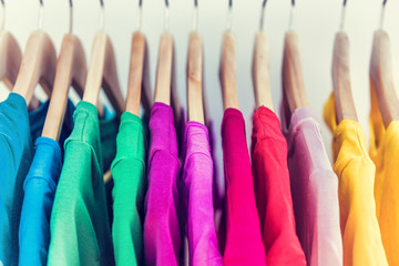 Fashion clothes on clothing rack closet. Closeup of colorful outfits on hangers in store closet or spring cleaning concept. Summer home wardrobe.