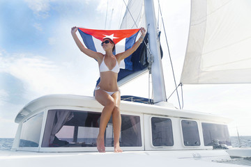 Beautiful brunette woman in white swimsuit is sitting with cuban flag on the stem of yacht