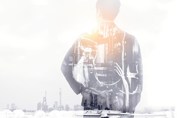 Industrial internet of things,disruption technology and industry 4.0 concept.Double exposure of business man holding engineer helmet and industrial machine with oil refinery background.