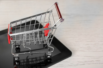 Online shopping concept. Tablet with mini market trolley on wooden background