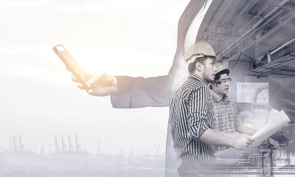 Smart construction , augmented reality in industry 4.0 concept. Double exposure of Business hand suit using mobile phone and two engineers using ar glasses with graphic popup,drone,crane,harbor.