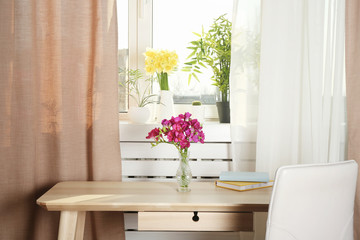 Vase with beautiful flowers on table