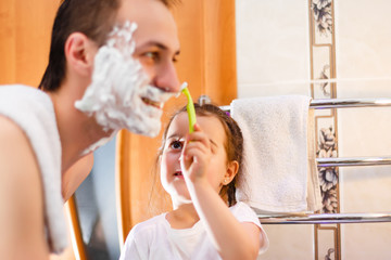 happy father and daughter having fun with shaving foam in the bathroom