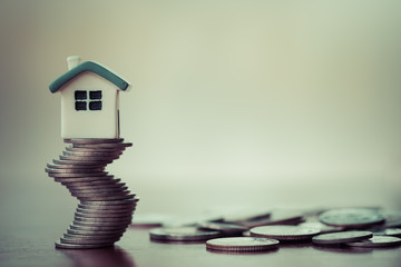 House model on coins stack. Concept for property ladder, mortgage and real estate investment .