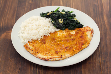 fried turkey with rice and spinach on the dish